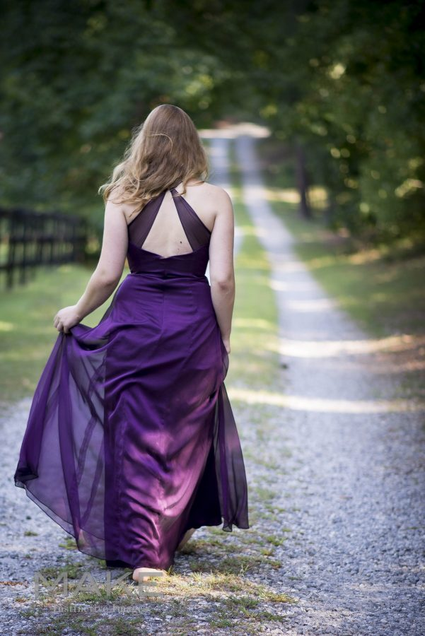 Young-woman-in-an-elegant-gown-on-a-dirt-road