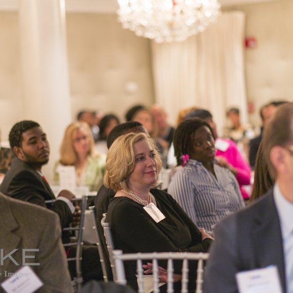 Corporate Event Photography in which a Crowd is watching a speaker present at an corporate event