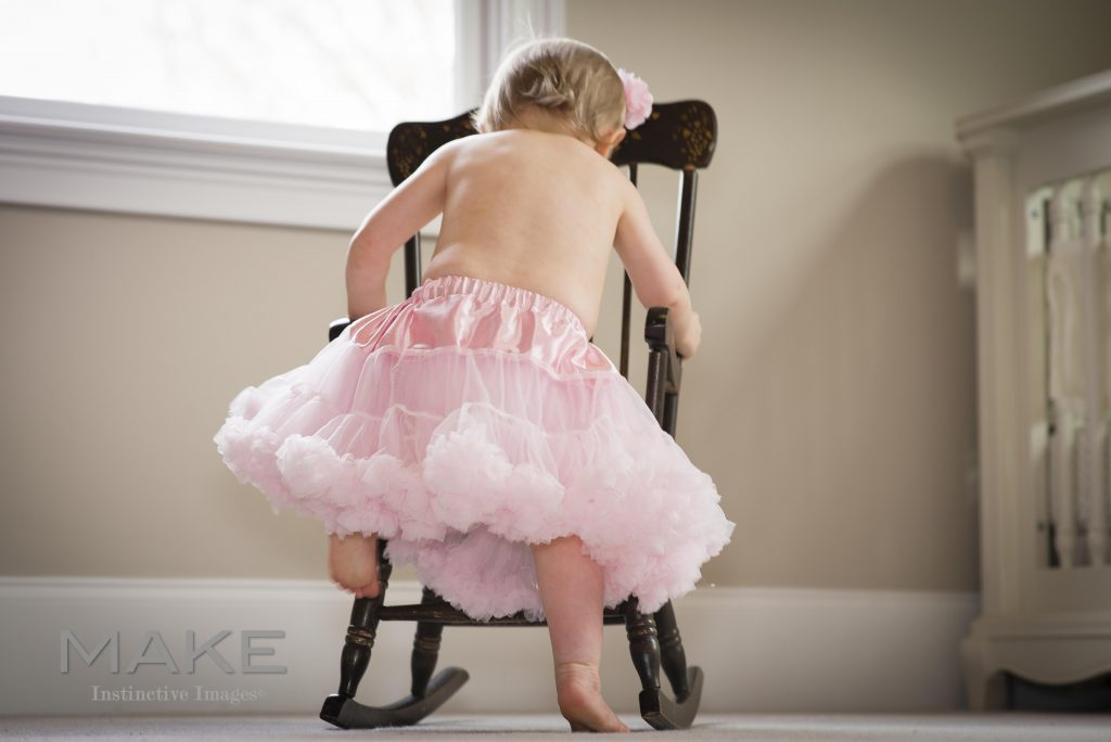 Toddler Girl in a tutu climbing into a chair