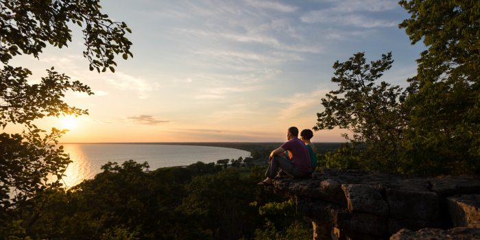 A-couple-sits-high-on-a-cliff-in-Adventure-Wedding-Photography-High-Cliff-Wisconsin